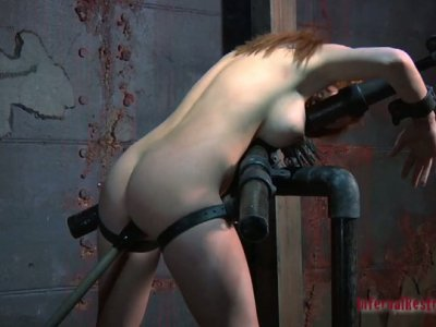 Redhead bitch Ashley Graham is poked with a sex machine while being locked up with handcuffs