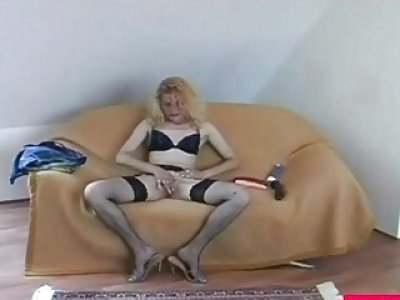 Blonde honey masturbates by using dildo on couch